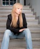 Tragende Blue Jeans der sexy Frau, die auf Treppe sitzt Stockfotografie
