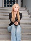 Tragende Blue Jeans der sexy Frau, die auf Treppe sitzt Stockfoto
