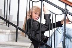 Tragende Blue Jeans der sexy Frau, die auf Treppe sitzt Lizenzfreies Stockfoto