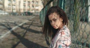 Tragende Bomberjacke der jungen Schönheit, die über Metallzaun aufwirft Stockbilder