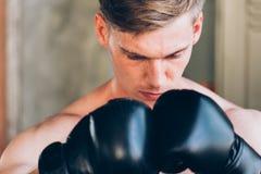 Tragende Boxhandschuhe des jungen kaukasischen männlichen Boxers vor Kampfwettbewerb stockfotos