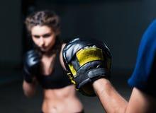 Tragende Boxhandschuhe des jungen Mädchens des Kämpferboxers geeigneten im Training Lizenzfreie Stockbilder