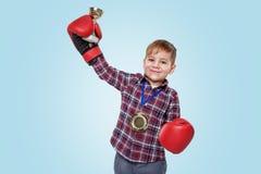 Tragende Boxhandschuhe des Jungen und feiern Erfolg mit goldener Trophäe lizenzfreie stockfotos