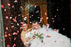 Tragende Braut des Bräutigams in seinen Armpaaren, Standesbeamten verlassend lizenzfreie stockfotos
