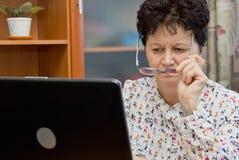 Tragende Brillen der älteren Frau und mit dem Notizbuch zu Hause arbeiten Stockfoto