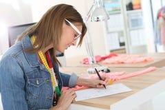 Tragende Brillen der Damenschneiderin, die Kleidung entwerfen lizenzfreie stockfotografie