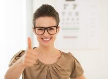 Tragende Brillen der Frau, die sich Daumen nahe Snellen-Diagramm zeigen lizenzfreie stockfotos
