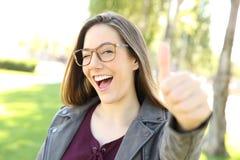 Tragende Brillen des lustigen Mädchens mit den Daumen oben Stockfotografie