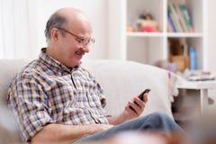 Tragende Brillen des reifen hispanischen Mannes, die Mitteilungen am Handy überprüfen stockfotos