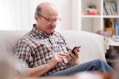 Tragende Brillen des reifen hispanischen Mannes, die Mitteilungen am Handy überprüfen lizenzfreies stockfoto