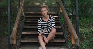Tragende Denimjacke des glücklichen stilvollen Mädchens, die auf hölzerner Treppe in einem Stadtpark sitzt stock video footage