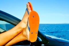 Tragende Flipflops des jungen Mannes, die in einem Auto nahe dem Ozean sich entspannen Stockfotografie
