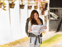 Tragende Freizeitbekleidung und Rucksack der jungen hübschen Frau, die vor der Kamera, glücklich lächelnd steht und halten Karte Stockbilder