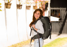Tragende Freizeitbekleidung und Rucksack der jungen hübschen Frau, die vor der Kamera glücklich lächelt, Wandererkonzept steht Stockfoto