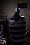 Tragende Gefängnisuniform des weiblichen Gefangenen, die mit ihrem zurück Ne steht Lizenzfreies Stockbild