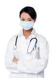 Tragende Gesichtsmaske des jungen weiblichen Chirurgen Lizenzfreie Stockfotos