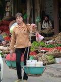 Tragende Gewürze und Gemüse der Frau am Straßenmarkt in Vietnam Stockfotos
