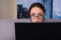Tragende Gläser der ernsten Frau, die zu Hause hinter den Laptop spähen Stockfotografie