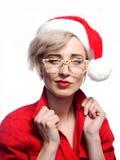 Tragende Gläser der Frau und eine Weihnachtskappe stockfotos