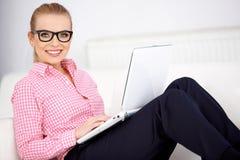 Tragende Gläser der hübschen Frau, die sich zu Hause entspannen Stockfotografie