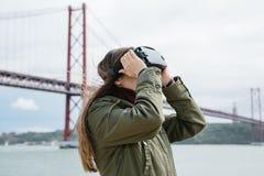 Tragende Gläser der virtuellen Realität des jungen schönen Mädchens 25. von April-Brücke in Lissabon im Hintergrund Das Konzept v Lizenzfreies Stockfoto