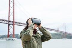 Tragende Gläser der virtuellen Realität des jungen schönen Mädchens 25. von April-Brücke in Lissabon im Hintergrund Das Konzept v Lizenzfreie Stockfotografie