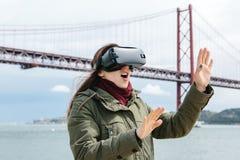 Tragende Gläser der virtuellen Realität des jungen schönen Mädchens 25. von April-Brücke in Lissabon im Hintergrund Das Konzept v Stockfotografie
