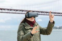 Tragende Gläser der virtuellen Realität des jungen schönen Mädchens 25. von April-Brücke in Lissabon im Hintergrund Das Konzept v Lizenzfreie Stockfotos