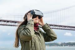 Tragende Gläser der virtuellen Realität des jungen schönen Mädchens 25. von April-Brücke in Lissabon im Hintergrund Das Konzept v Stockbilder