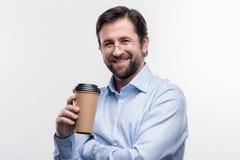 Tragende Gläser des bärtigen Mannes, die den Mitnehmerkaffee hat Bruch halten lizenzfreie stockfotos