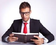 Tragende Gläser des Geschäftsmannes, die ein Buch lesen Stockbild