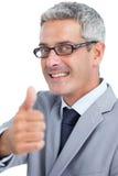 Tragende Gläser des hübschen Geschäftsmannes und sich zeigen Daumen Stockbild