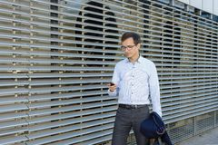 Tragende Gläser des jungen Geschäftsmannes des gut aussehenden Mannes im Hemd Freiberufler hält Telefon lizenzfreies stockbild