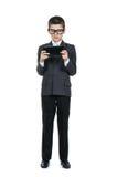 Tragende Gläser des Jungenschülers Intelligenter Junge mit einer Tablette in den Händen Das Konzept der modernen Bildung Stockfoto