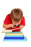 Tragende Gläser des kleinen Jungen, die ein Buch mit Vergrößerungs-glas lesen Stockfoto