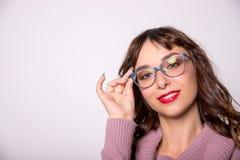 Tragende Gläser des Schönheitsmode-Mädchens, die leeren Kopienraum, weißen Hintergrund zeigen Glückliches Mädchendarstellen modis stockfotografie