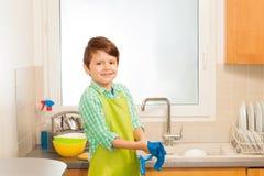 Tragende Gummihandschuhe des netten Jungen vor Abwasch Lizenzfreie Stockfotografie