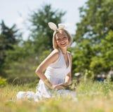 Tragende Häschenohren der glücklichen jungen Mutter, lächelndes auf Decke draußen sitzen Stockfotografie