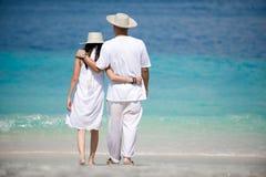 Tragende Hüte der romantischen Paare auf dem Strand Stockfotos