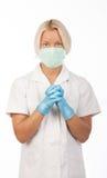 Tragende Handschuhe der überzeugten blonden Krankenschwester Lizenzfreie Stockfotos