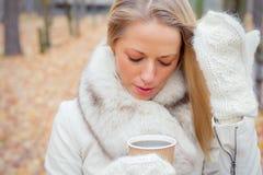 Tragende Handschuhe der Frau und trinkender Kaffee Stockfotos