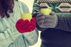 Tragende Handschuhe der jungen Paare halten Schalen mit Tee Lizenzfreies Stockbild