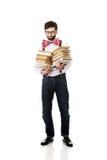 Tragende Hosenträger des Mannes mit Stapel Büchern Stockbilder