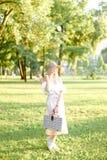 Tragende Hutstellung des jungen amerikanischen Mädchens im Park mit Tasche stockbild