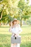Tragende Hutstellung des jungen netten Mädchens im Park mit Tasche stockbilder