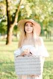 Tragende Hutstellung des jungen reizend Mädchens im Park mit Tasche lizenzfreie stockbilder