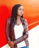 Tragende Jacke der afrikanischen Frau des Porträts in der Stadt über Rot Lizenzfreies Stockfoto