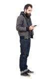 Tragende Jacke des jungen Hippies über dem mit Kapuze Sweatshirt, das am Handy schreibt Lizenzfreies Stockfoto