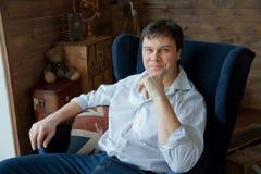 Tragende Jeans des gutaussehenden Mannes, die auf Stuhl sitzen lizenzfreie stockfotografie