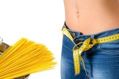 Tragende Jeans des jungen Mädchens nach Diät- und Lebensmittelhintergrund Lizenzfreie Stockbilder